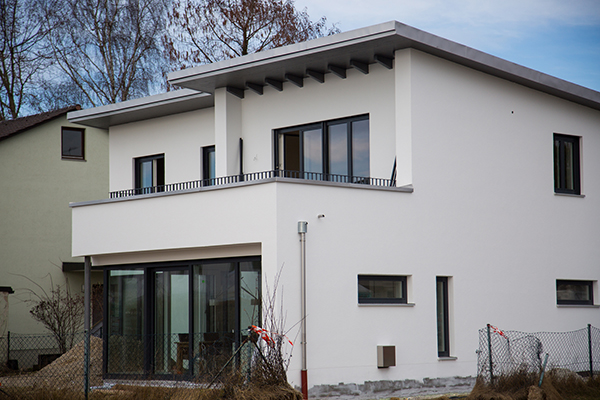 A huge residential property that has a terrace and a flat roof.